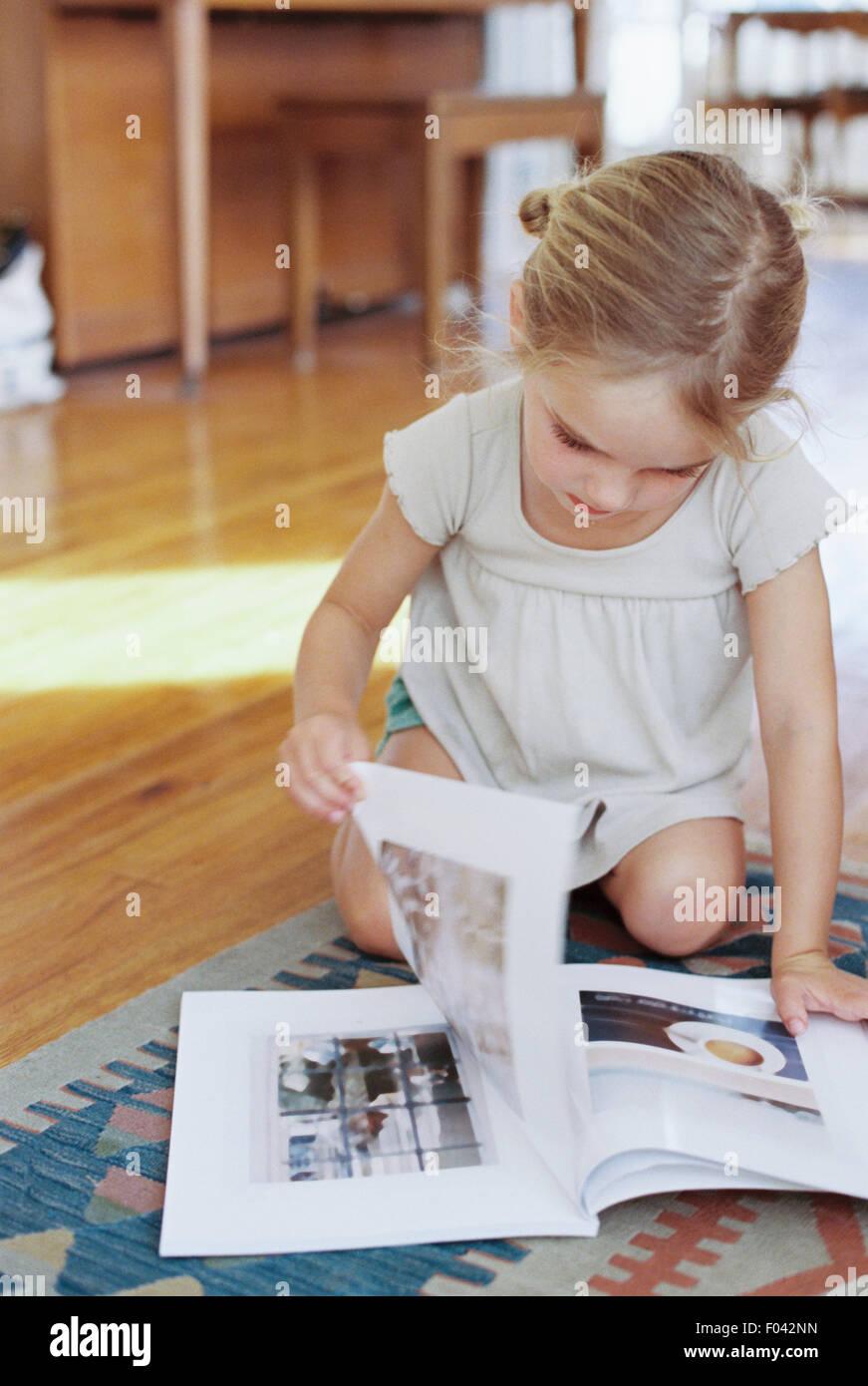 Giovane ragazza seduta sul pavimento, la lettura di un lifestyle magazine. Immagini Stock