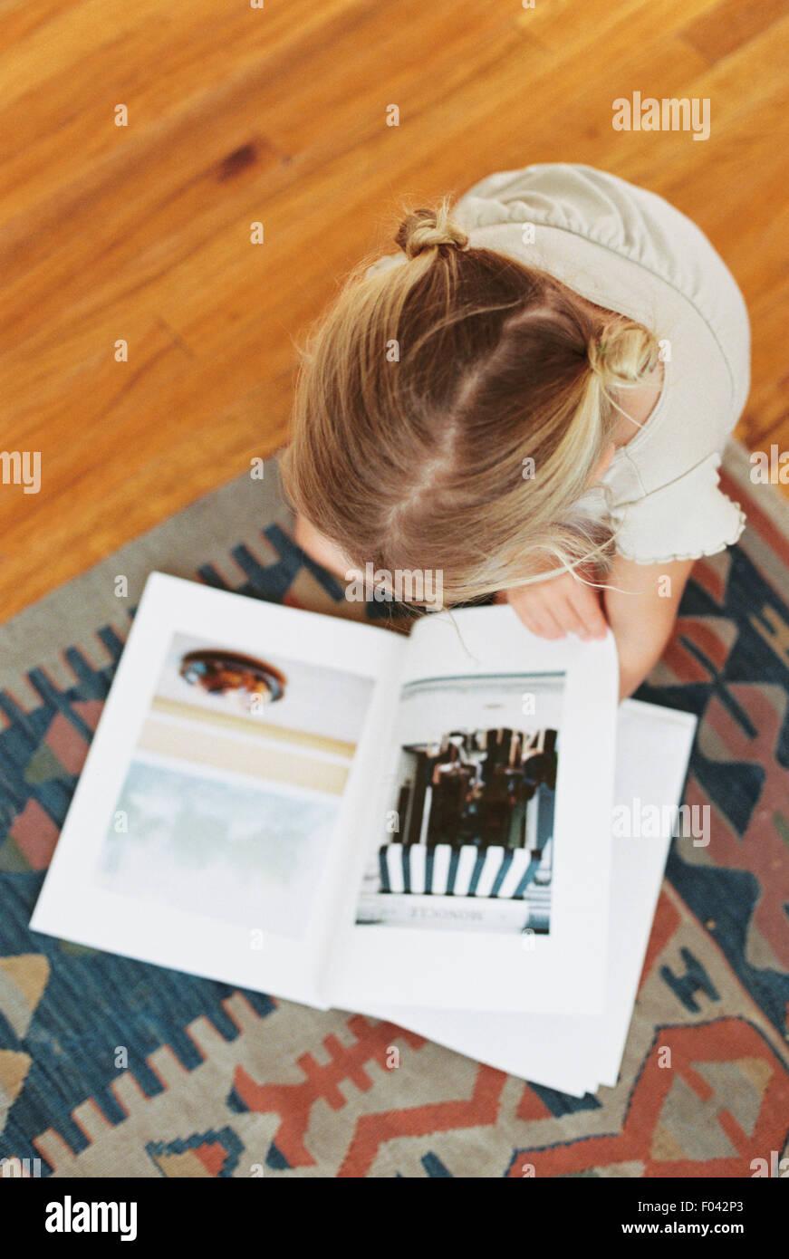 Giovane ragazza seduta sul pavimento, la lettura di un libro, vista da sopra Immagini Stock
