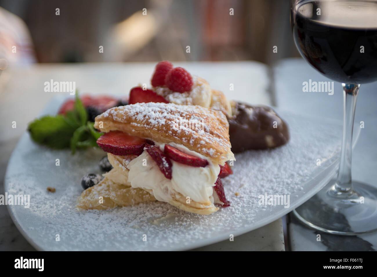 Dolce italiano servito con un bicchiere di vino rosso Immagini Stock