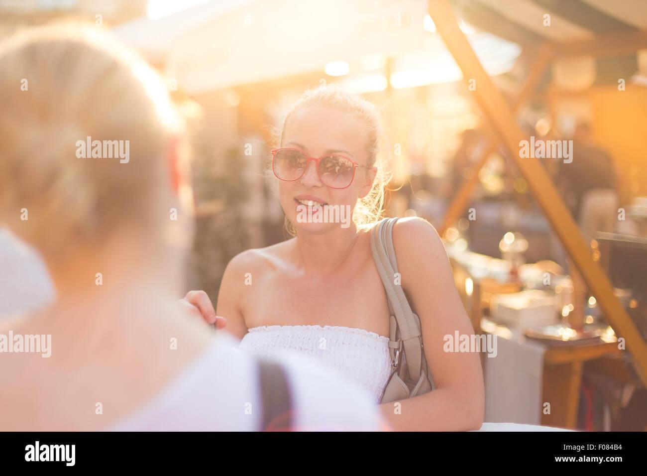 Amici di sesso femminile godendo di una conversazione sul mercato. Immagini Stock