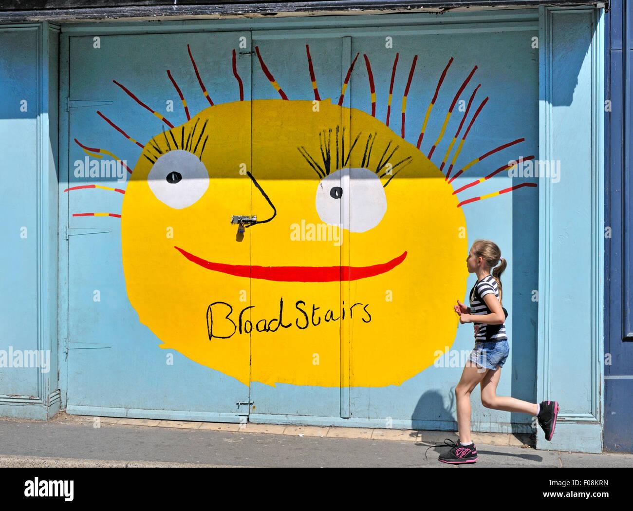 Broadstairs Kent, Inghilterra, Regno Unito. Giovane ragazza in esecuzione passato un dipinto di negozio in strada Immagini Stock