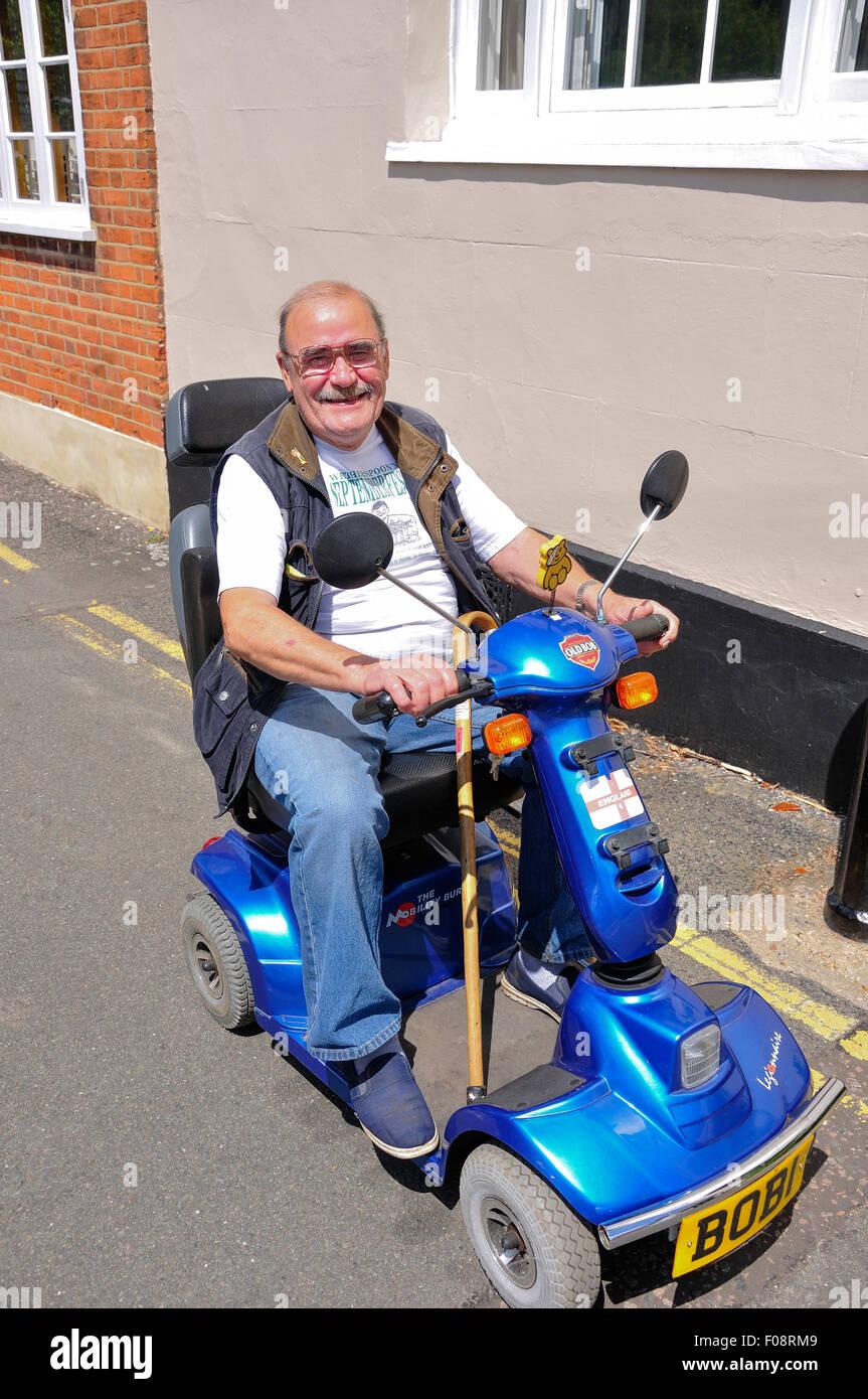 Uomo sorridente sulla mobilità scooter, la terrazza, Wokingham, Berkshire, Inghilterra, Regno Unito Immagini Stock
