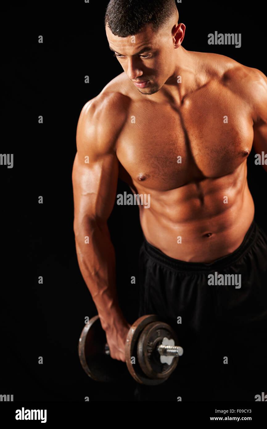Muscolare di giovane uomo che lavora fuori con pesanti dumbbell Immagini Stock