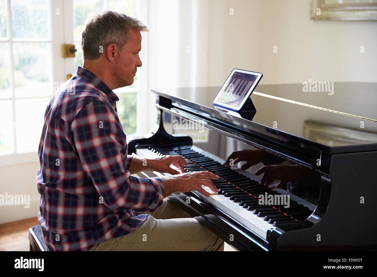 Uomo di imparare a suonare il piano utilizzando tavoletta digitale applicazione Immagini Stock