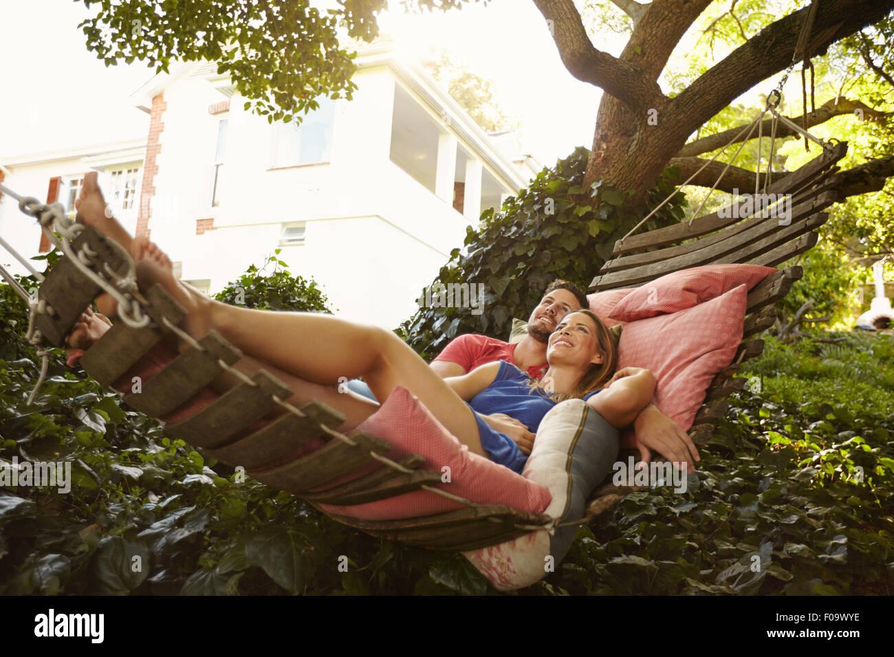 Ritratto di un affettuoso coppia giovane sdraiato su un amaca guardando lontano sorridente. Romantico giovane uomo Immagini Stock