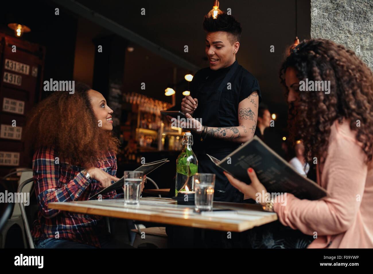 Giovane donna con un amico ordinare al cameriere azienda digitale compressa. Due donne sedute presso il cafe tenendo Immagini Stock