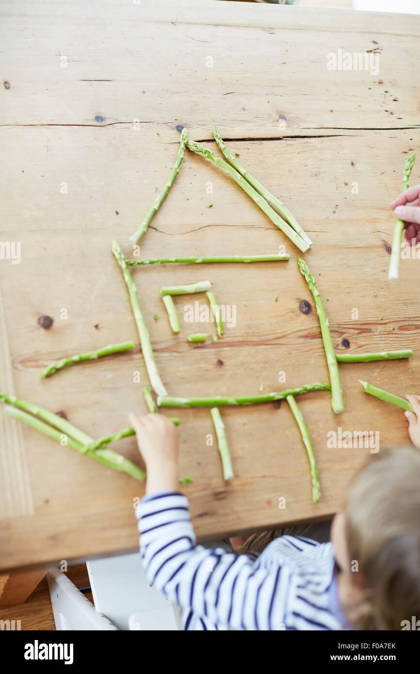 Ragazzo giocando con gli asparagi sul tavolo da pranzo Immagini Stock