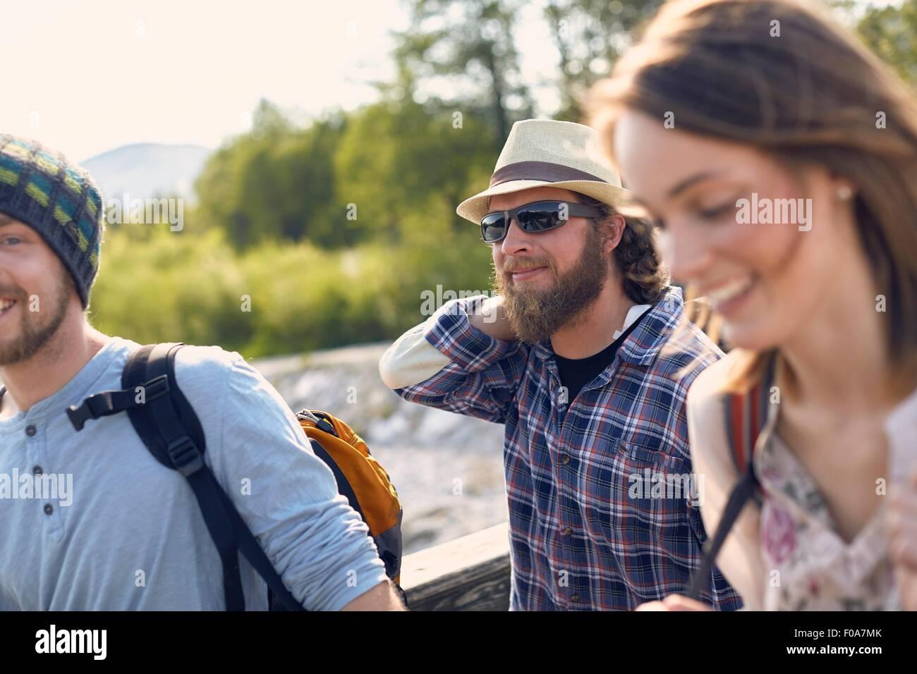 Tre persone che camminano insieme trasportano zaini, sorridente Immagini Stock