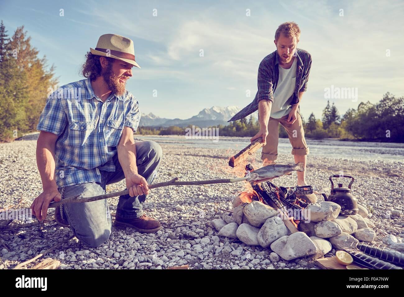 Gli uomini adulti cucinare il pesce attaccato al ramo sopra il fuoco, Wallgau, Baviera, Germania Immagini Stock