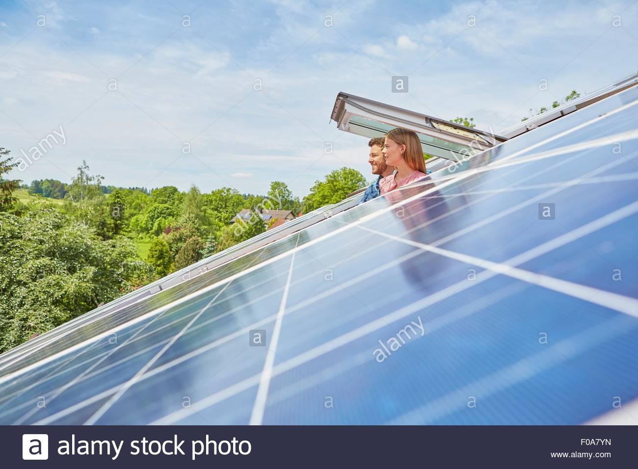 Coppia giovane guardando fuori della finestra di pannelli solari sul tetto Immagini Stock
