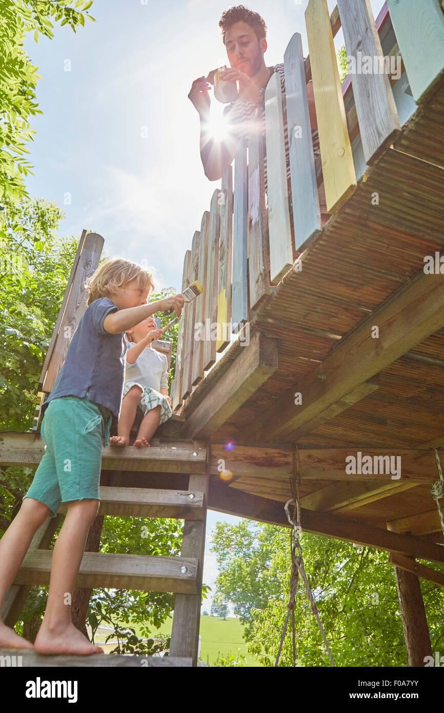 Padre e i due figli, pittura tree house, a basso angolo di visione Immagini Stock
