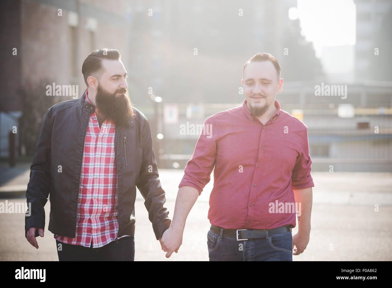 Coppia gay camminando mano nella mano su strada Immagini Stock