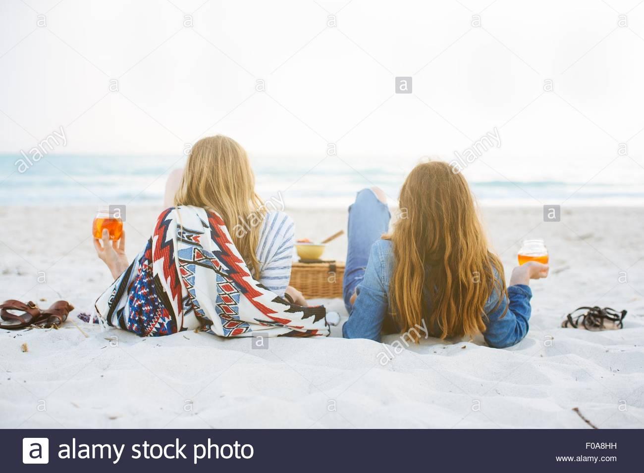Vista posteriore di due giovani amici di sesso femminile reclinata su spiaggia affacciata sul mare Immagini Stock