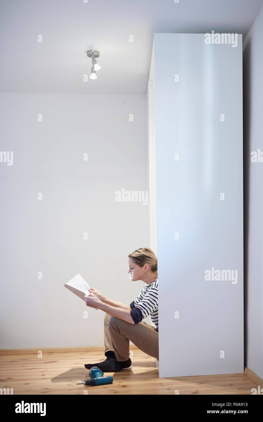 Donna matura leggendo il manuale di istruzioni per l'armadio flatpack Immagini Stock