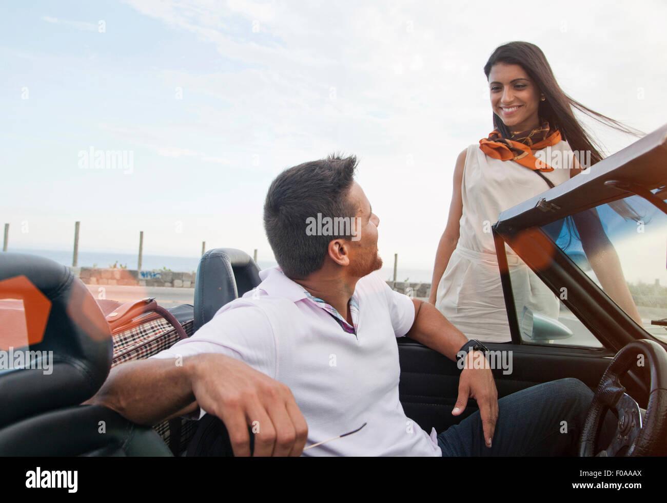 Uomo in autovettura convertibile, donna in piedi accanto a AUTO, sorridente Foto Stock