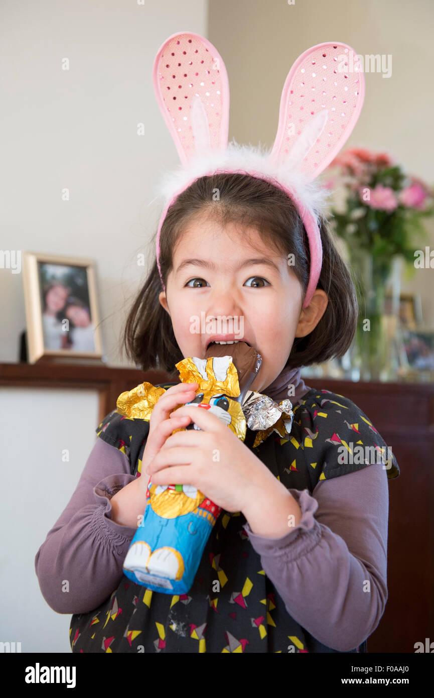 Ragazza giovane indossando orecchie di coniglietto, appena circa a mordere coniglio di cioccolato Immagini Stock