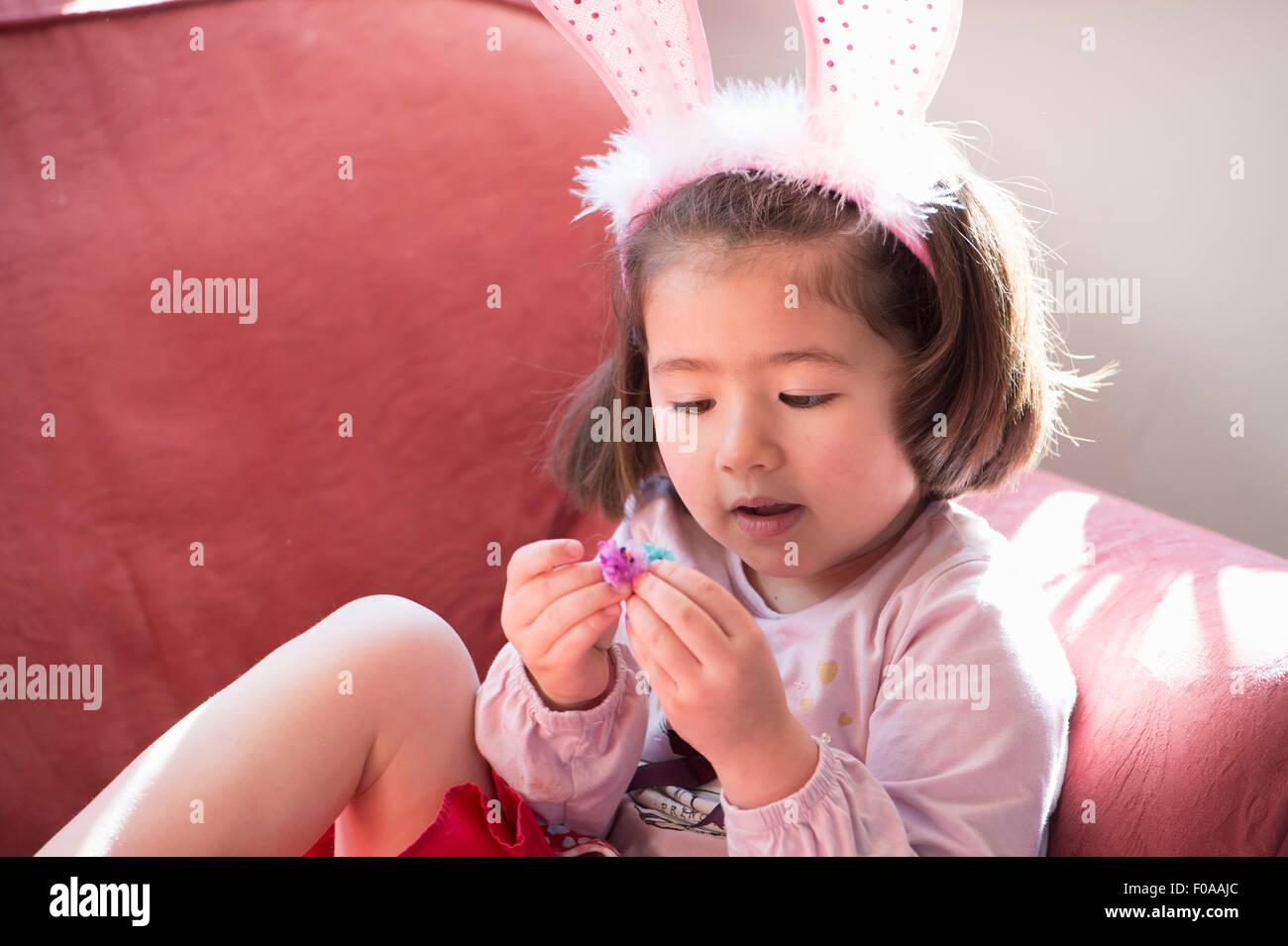 Ragazza giovane indossando orecchie di coniglietto, guardando a fluffy pulcino di Pasqua Immagini Stock