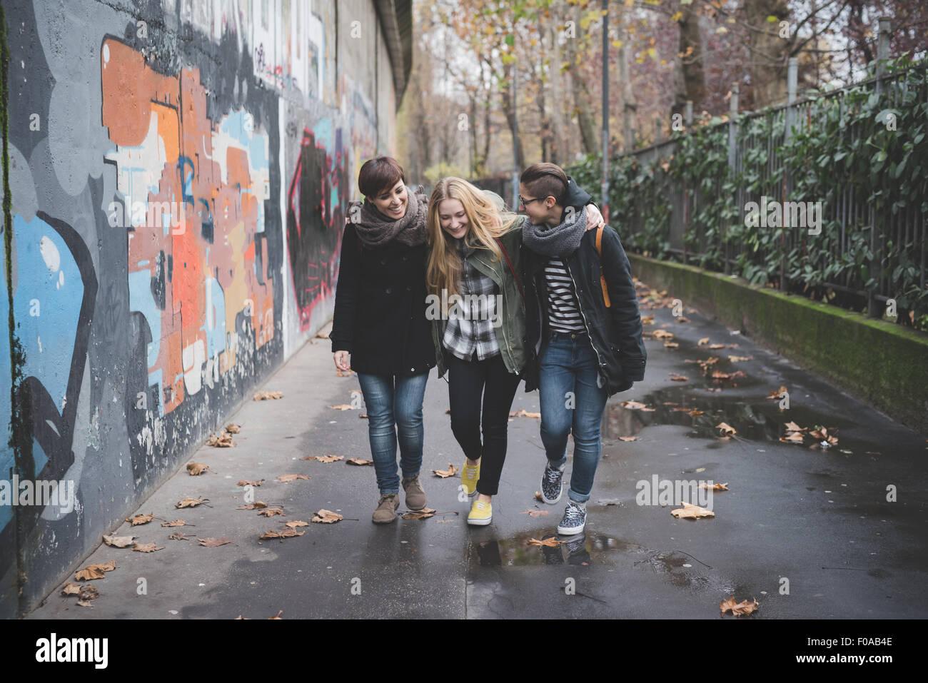 Le tre sorelle a piedi dal muro di graffiti Immagini Stock