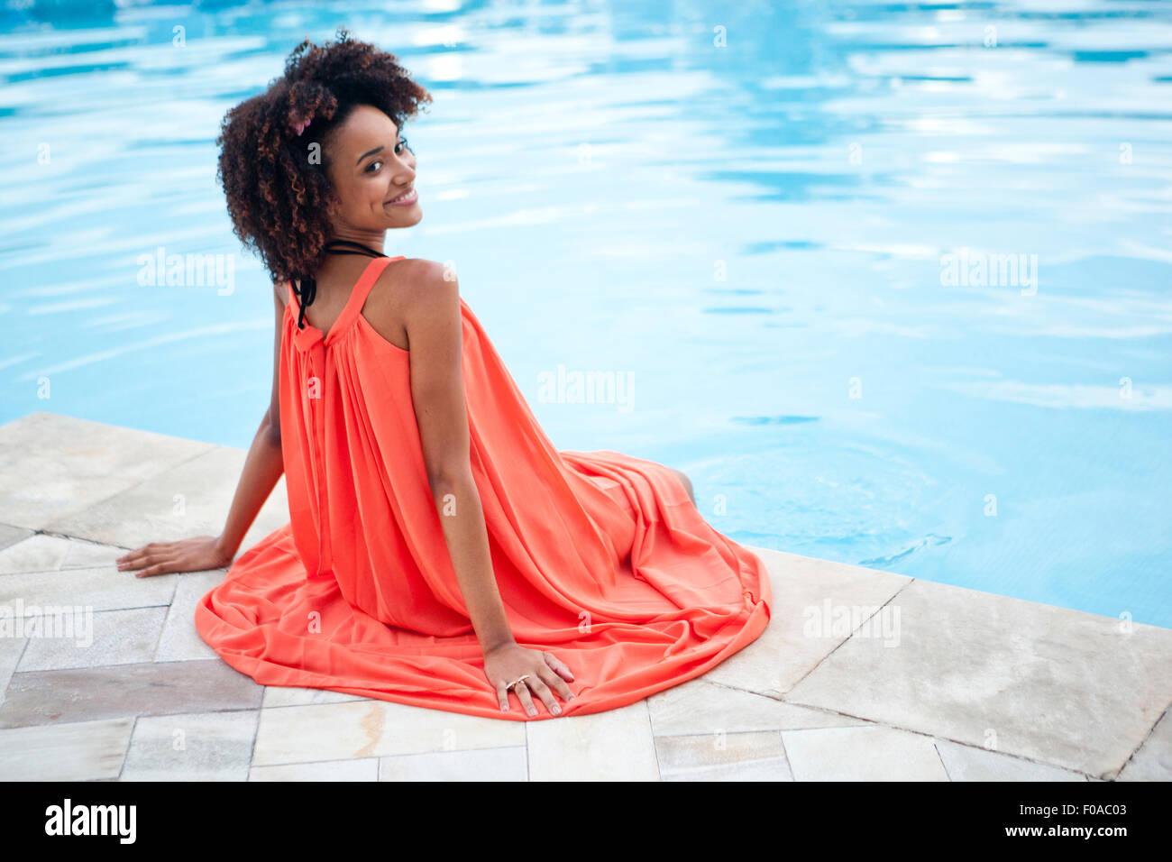 Ritratto di giovane donna che indossa abiti di colore arancione seduto al hotel piscina, Rio de Janeiro, Brasile Immagini Stock