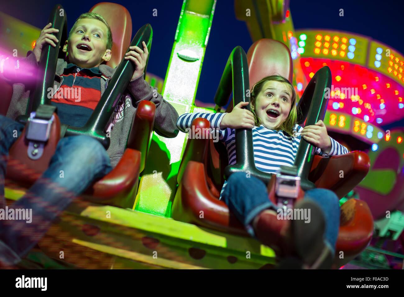 Sorella e fratello su fairground ride di notte Immagini Stock