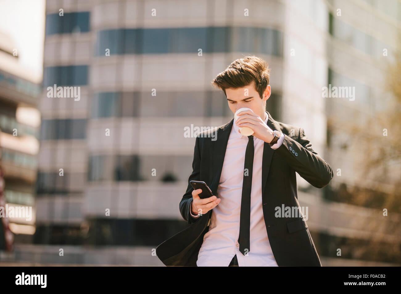 Giovane imprenditore bere take away caffè mentre la lettura di testi dello smartphone Immagini Stock