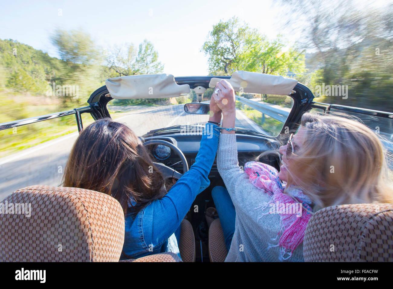 Due donne mature, tenendo le mani, in autovettura convertibile, vista posteriore Immagini Stock