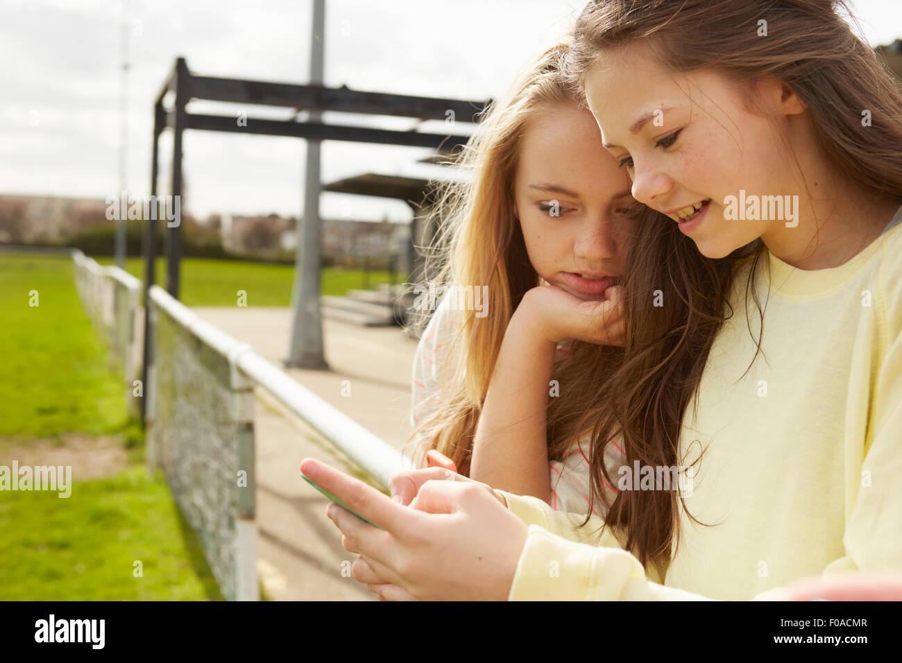 Due ragazze dello smartphone di lettura dei messaggi di testo Immagini Stock