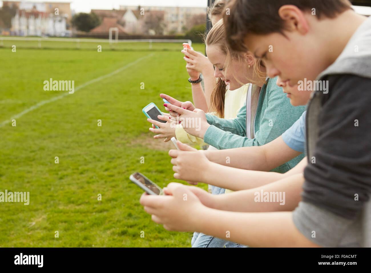 Fila di cinque ragazzi e ragazze dello smartphone di lettura dei messaggi di testo al campo di calcio Immagini Stock
