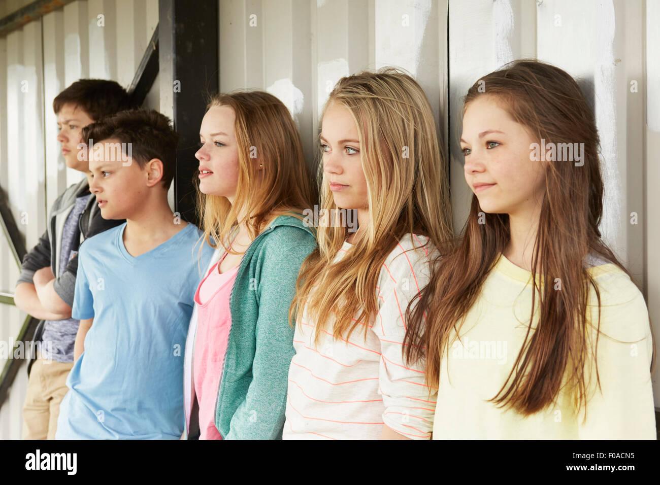 Fila di cinque ragazze e ragazzi guardando fuori dal rifugio Immagini Stock