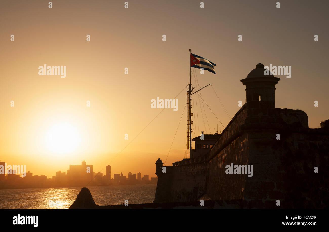 Bandiera cubana oltre El Morro Fortezza al tramonto, Havana, Cuba Immagini Stock