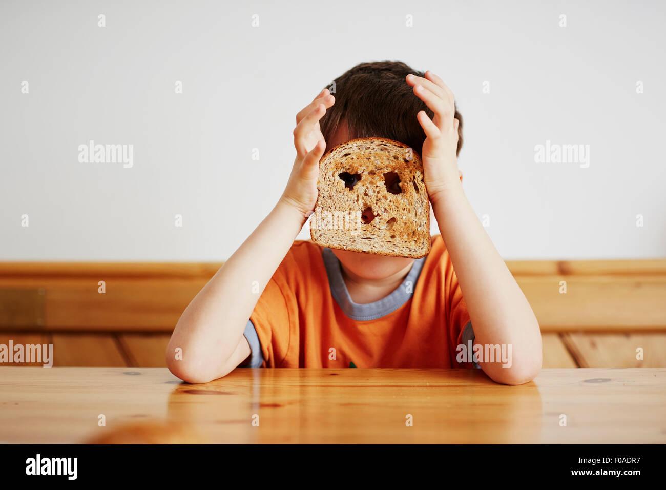 Ragazzo che ricopre la faccia con toast Immagini Stock