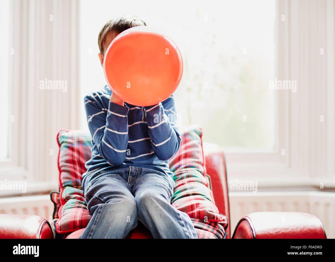 Giovane ragazzo palloncino di contenimento nella parte anteriore del viso Immagini Stock