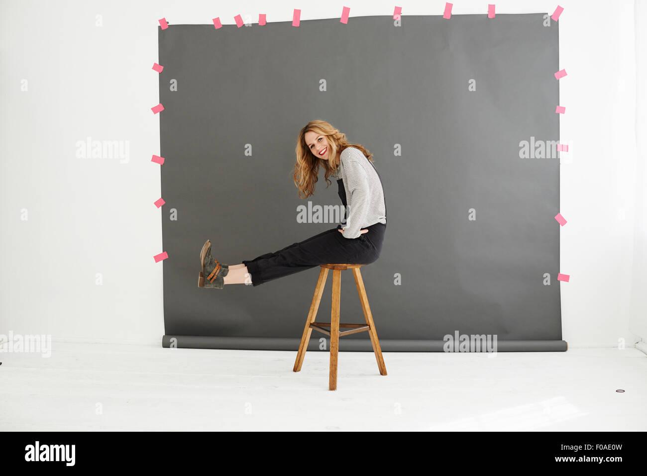Donna su uno sgabello davanti dei fotografi di sfondo Immagini Stock