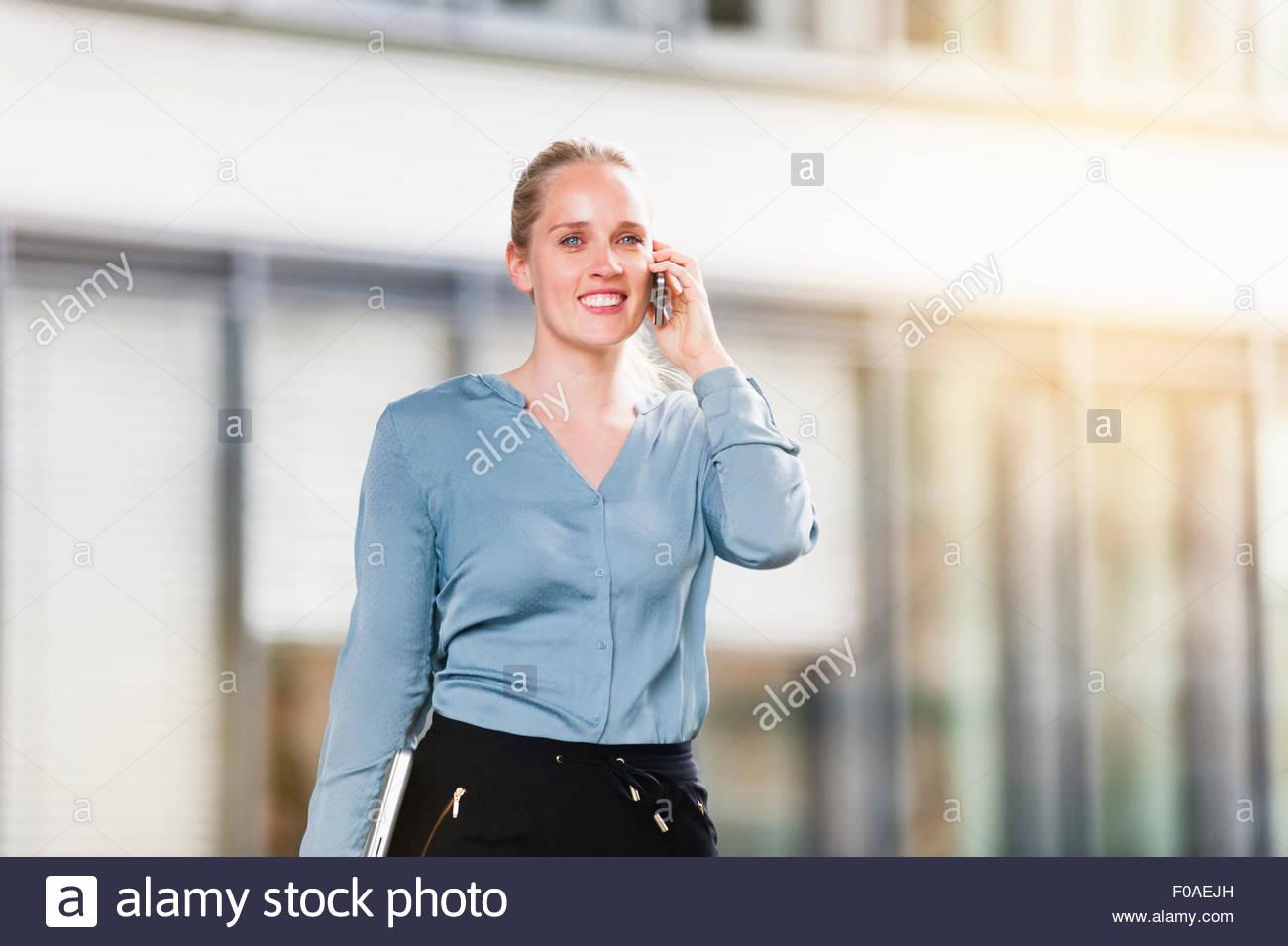 Giovane donna, tenendo il laptop e parlando al telefono cellulare Immagini Stock