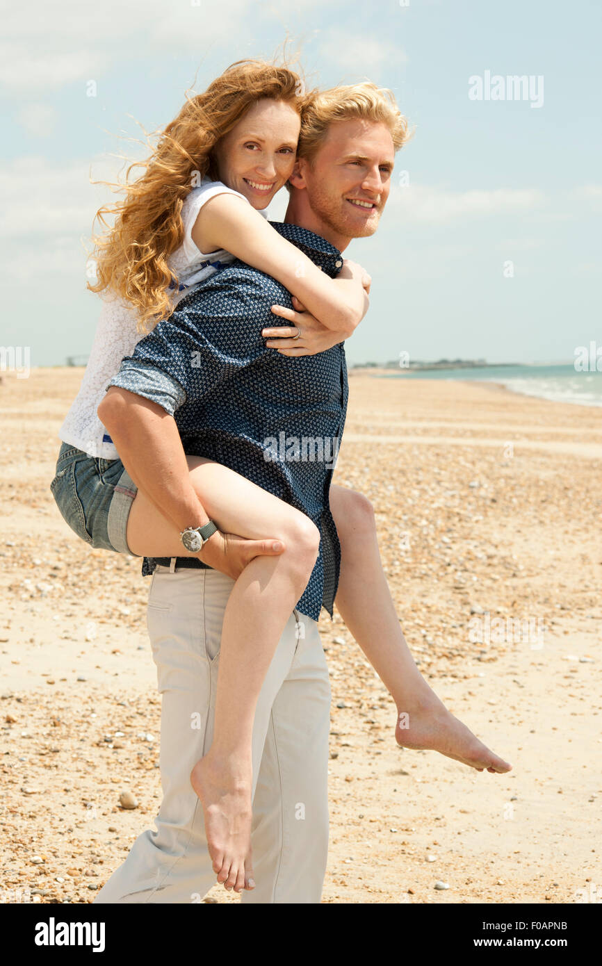 L uomo dando ragazza un piggyback in spiaggia Immagini Stock