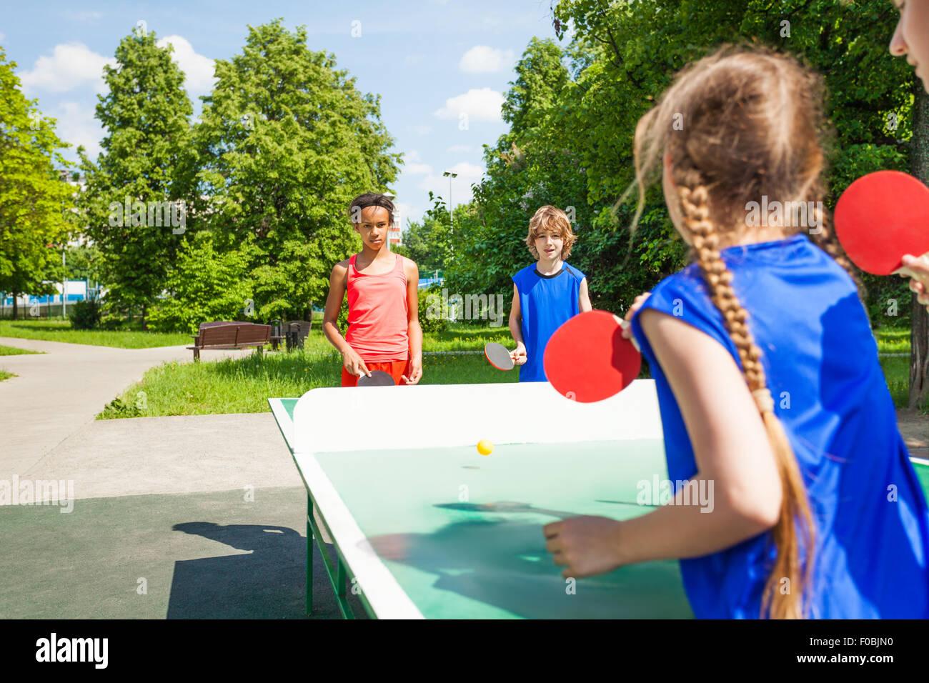 Quattro amici internazionali giocare a tennis da tavolo Immagini Stock