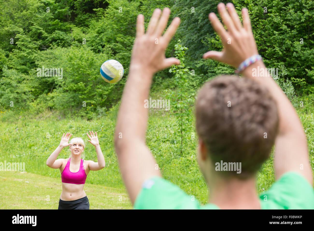 Coppia giovane giocando a pallavolo in park. Immagini Stock
