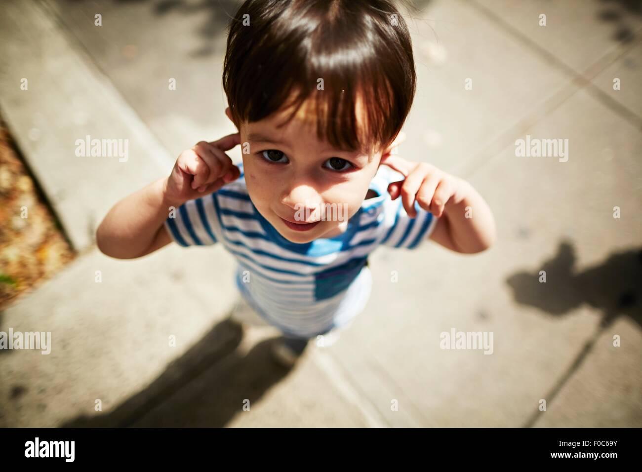 Ritratto di ragazzo di mettere le dita nei suoi orecchi su strada Immagini Stock