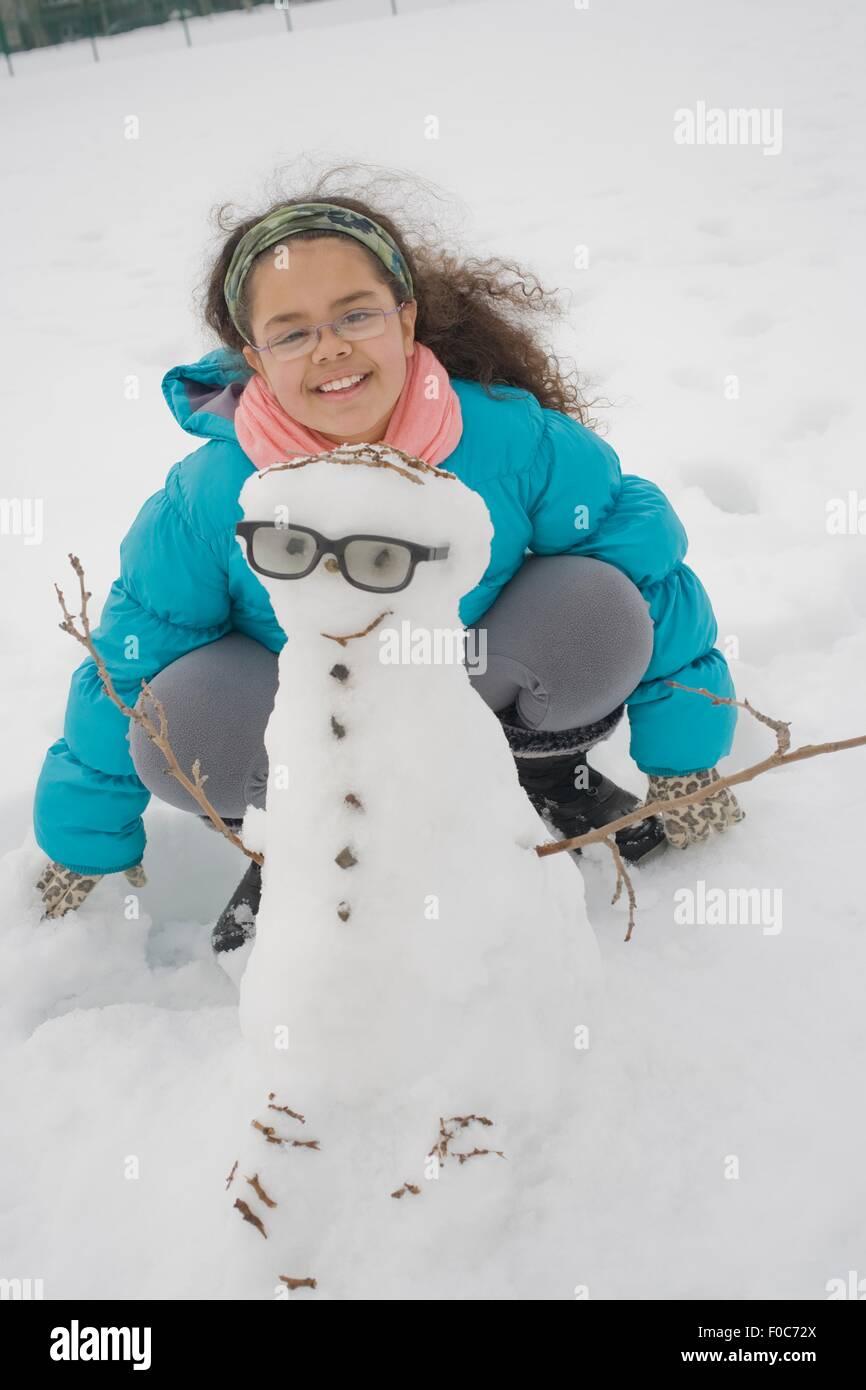 Ragazza giovane edificio pupazzo di neve Immagini Stock
