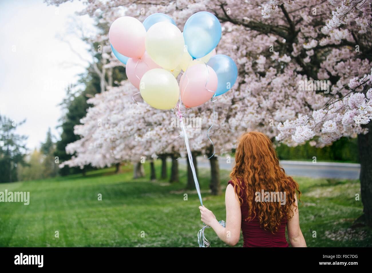 Vista posteriore della giovane donna con ondulata lungo i capelli rossi e il mazzetto di palloncini in primavera Immagini Stock