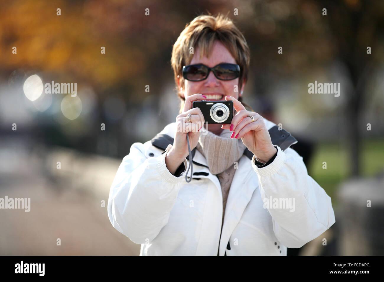 Una donna di mezza età, un turista, tenendo la sua fotocamera per scattare una foto verso il fotografo. Lei Immagini Stock