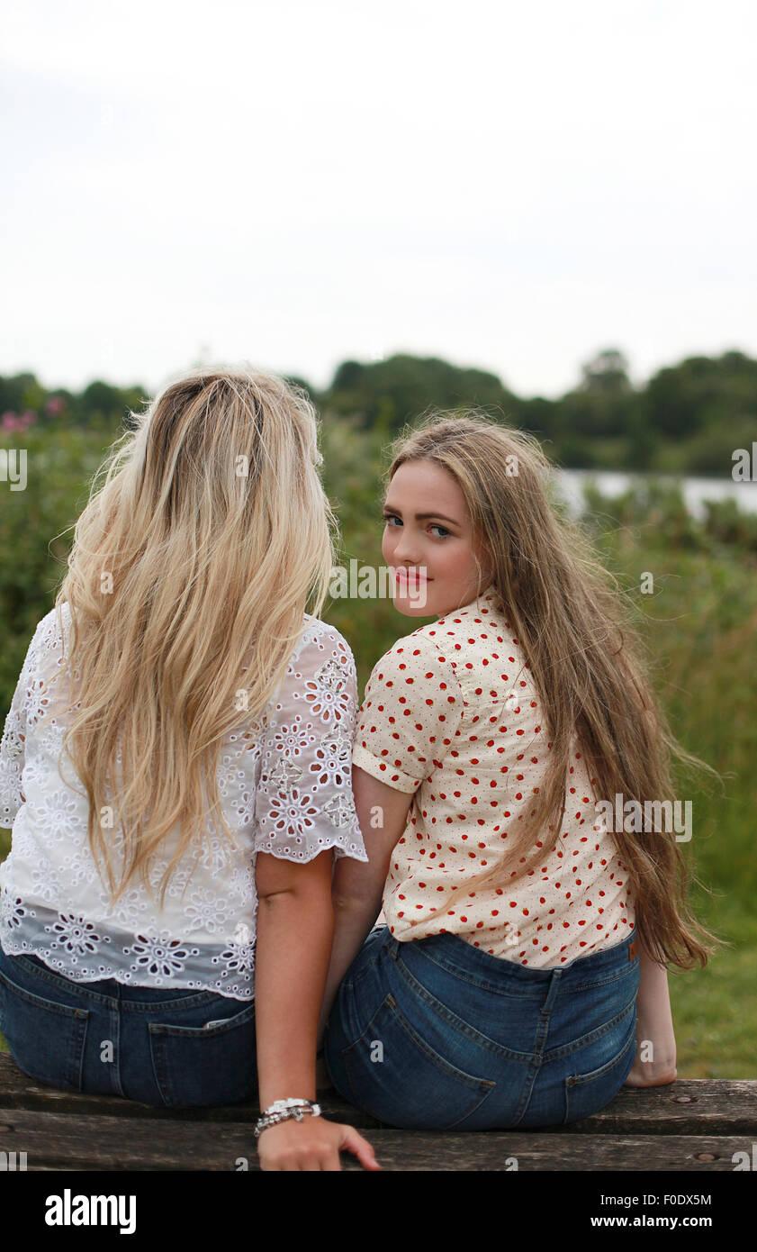 Due ragazze adolescenti a guardare lontano e uno che guarda alla fotocamera Immagini Stock