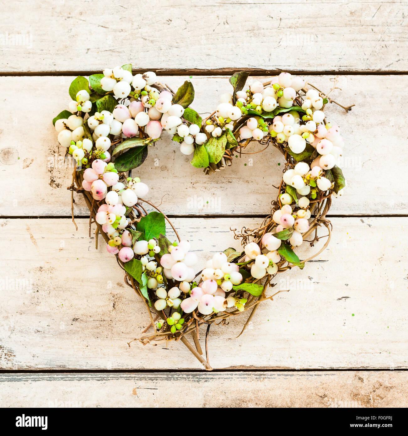 A forma di cuore ghirlanda snowberry su legno Immagini Stock