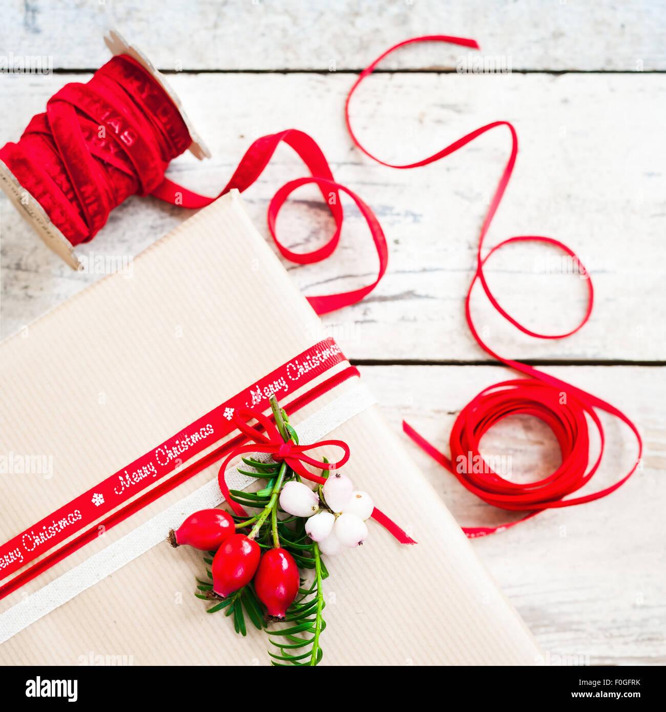 Regalo semplice avvolto con carta marrone e decorato con un nastro rosso e bacche Immagini Stock
