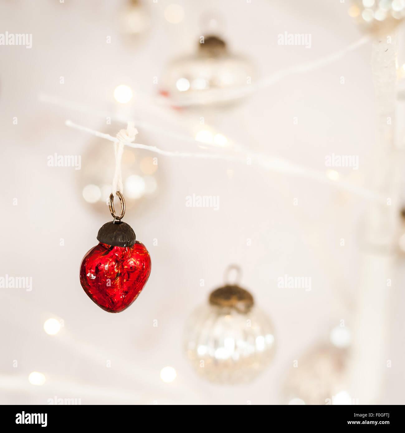 Primo piano di un cuore rossa a forma di pallina di vetro con argento e baubles bokeh in background Immagini Stock