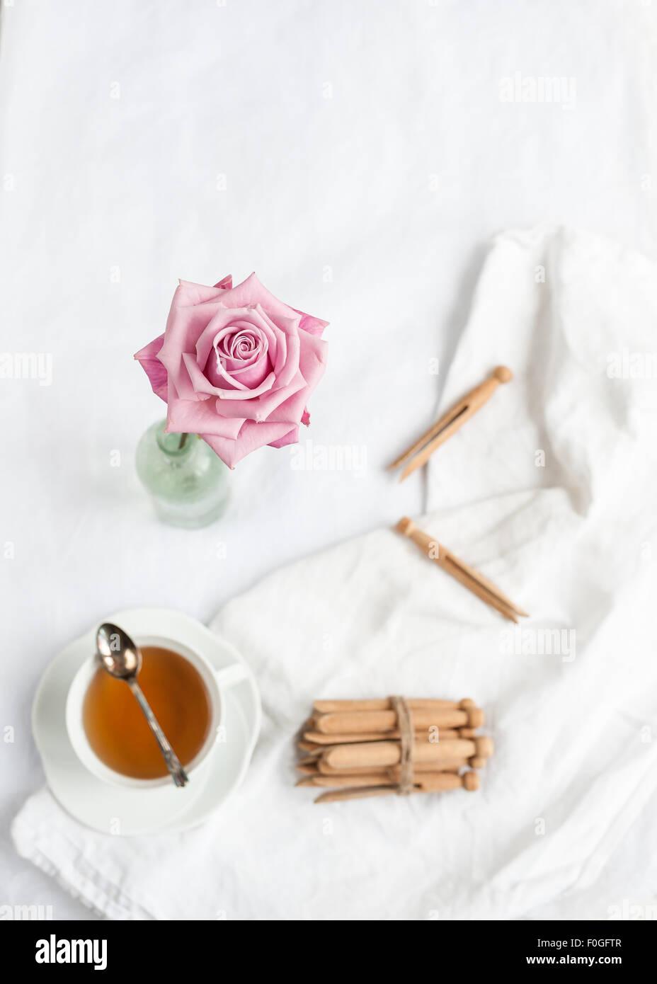 Una sola rosa rosa nel fuoco, con sfondo sfocato di tessuto bianco, tazzina con cucchiaino e dolly mollette Immagini Stock