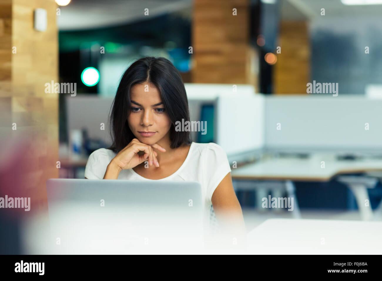 Ritratto di un grave imprenditrice utilizzando computer portatile in ufficio Immagini Stock