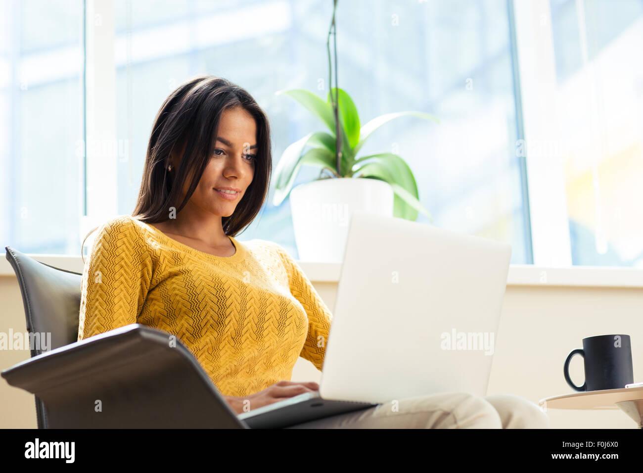 Felice casual imprenditrice seduto sulla sedia da ufficio con computer portatile in ufficio Immagini Stock