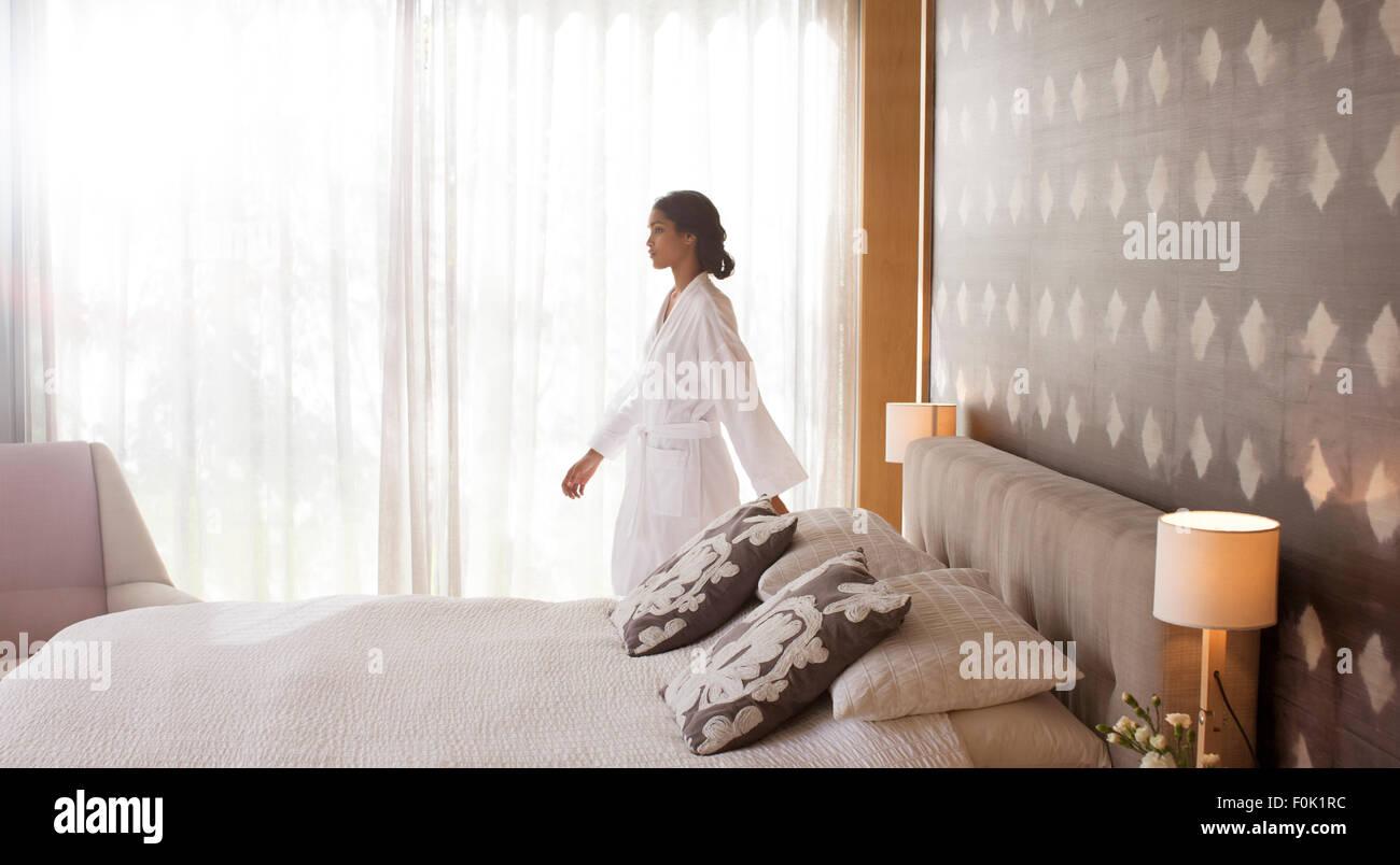 Donna in accappatoio a piedi in camera da letto Immagini Stock