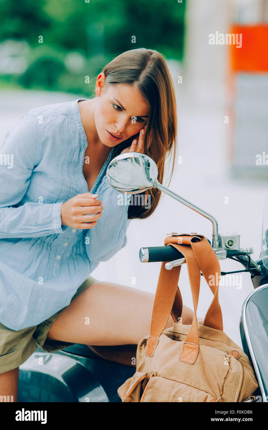 Giovane donna su scooter guardando nel retrovisore Immagini Stock